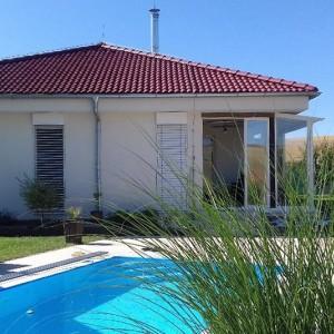 Světlý dům postavený jako dřevostavba s červenou střechou a zahradní bazén