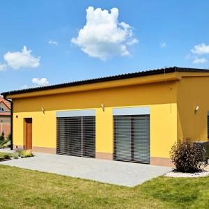 Žlutý rodinný dům postavený jako  přízemní dřevostavba - bungalov.
