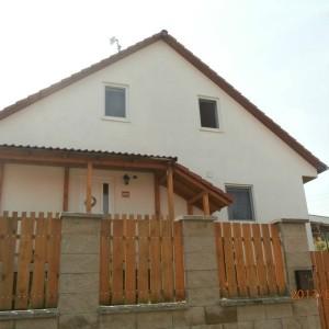 Světlá energeticky úsporná dřevostavba s červenou střechou nedaleko Kladna