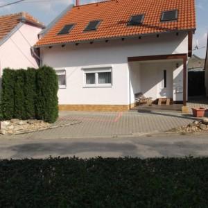 Bílý energeticky úsporný dům postavený jako dřevostavba s červenou střechou v Křižanovicích