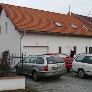 Bílá energeticky úsporná dřevostavba s červenou střechou v Olomouci